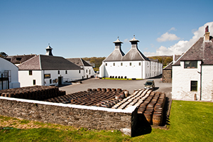 A photo of the Ardbeg Whiskey Distillery with barrels in front of the building